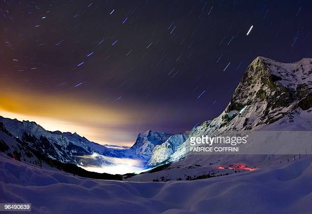 This long night exposure photo taken on late January 13 2010 in Wengen shows Swiss famous north face of the Eiger mountain overlooking the ressort of...