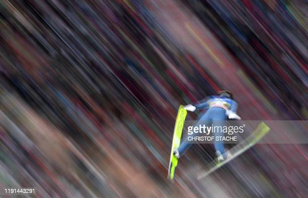 This long time exposure picture shows Dominik Peter from Switzerland soaring through the air during his qualifications jump of the FourHills Ski...