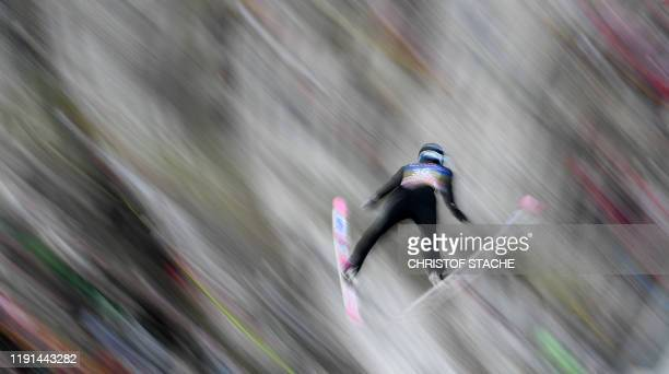 This long time exposure picture shows Jakub Wolny of Poland soaring through the air during his qualifications jump of the FourHills Ski Jumping...