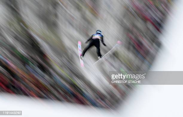TOPSHOT This long time exposure picture shows Jakub Wolny of Poland soaring through the air during his qualifications jump of the FourHills Ski...