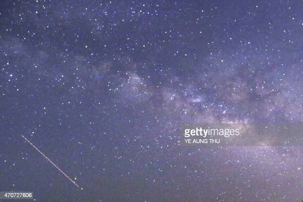 This longexposure photograph taken on April 23 2015 on Earth Day shows Lyrids meteors shower passing near the Milky Way in the clear night sky of...