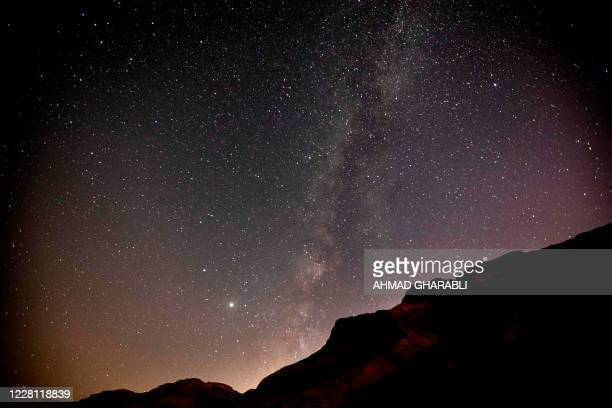 This long-exposure picture taken early on August 20, 2020 shows a view of the Milky Way galaxy rising in the sky above the Judaean mountains in the...