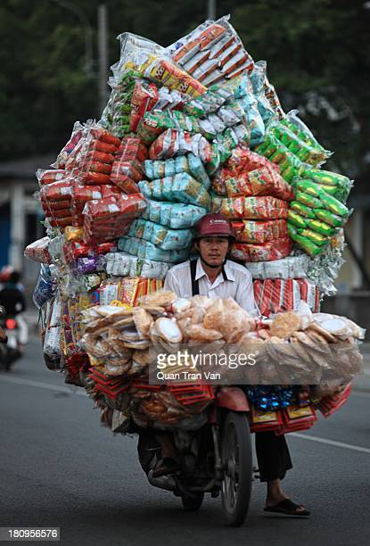 This man is carrying a heap of snack bags on his motorbike to the market in the early morning. Image was taken on the Y bridge of Ho Chi Minh city,...