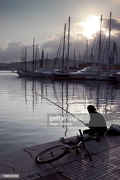 CONTENT] This man is fishing in Palma de Mallorca harbour Spain