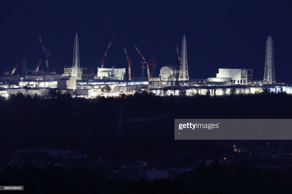 This March 10, 2018 picture shows the troubled Fukushima Daiichi nuclear power plant being lit up in Okuma, Fukushima prefecture, on the eve of the seventh anniversary of the 2011 Great East japan earthquake. Japan marked on March 11 the seventh anniversary of a deadly earthquake, tsunami and nuclear disaster that devastated its northeastern coast and left about about 18,500 people dead or missing. / AFP PHOTO / JIJI PRESS / - / Japan OUT