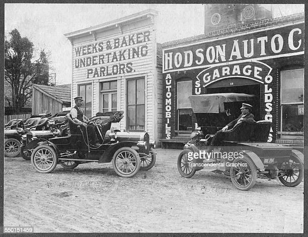 This mounted silver print photograph taken outside an early auto garage and the storefront for an undertaker is made somewhere circa 1905