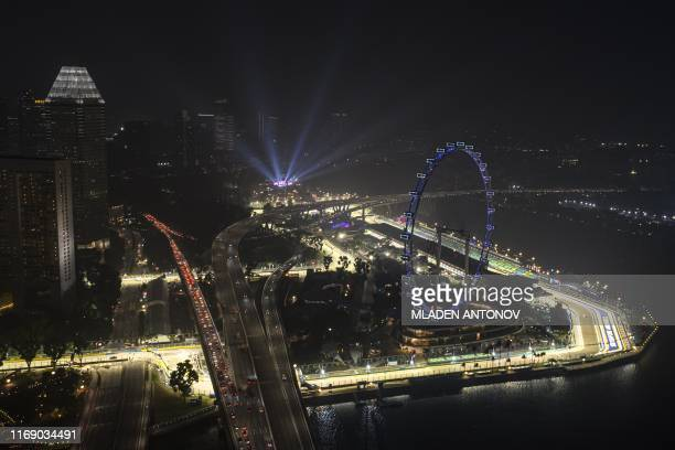 TOPSHOT This night time overview shows the Formula One Singapore Grand Prix at the Marina Bay Street Circuit illuminated race track blanketed by haze...