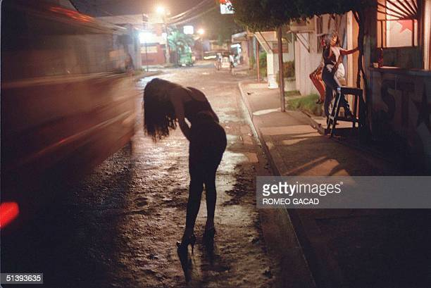 This November 28 October 1997 photo which is part of a documentary on AIDS shows a transvestite trying to attract customers in an area near the...