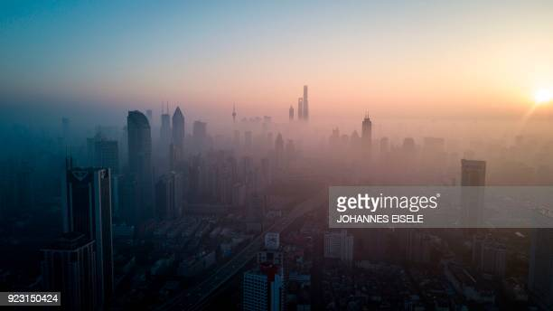 TOPSHOT This overhead photo shows the sun rising above the skyline of Shanghai on a polluted day on February 23 2018 / AFP PHOTO / Johannes EISELE