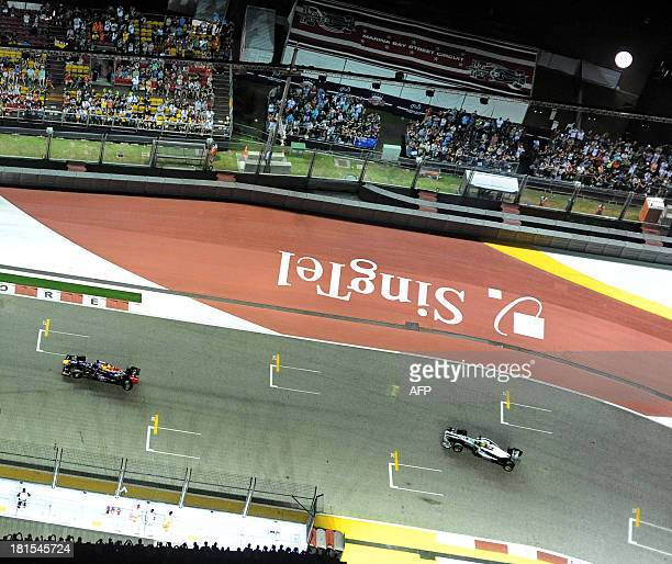 This overview shows Red Bull driver Sebastian Vettel of Germany leading Mercedes driver Nico Rosberg of Germany during the Formula One Singapore...