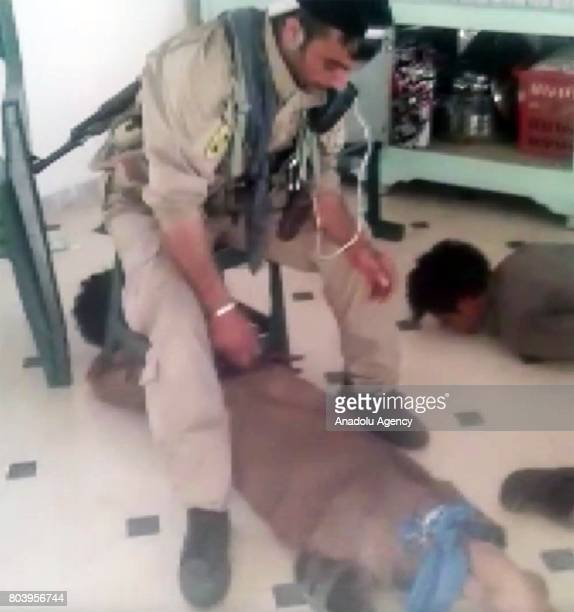 This photo captured from a video shows PYD/PKK members torturing two civilians in Mansoura town western Raqqa Syria on May 2017 It is seen in the...
