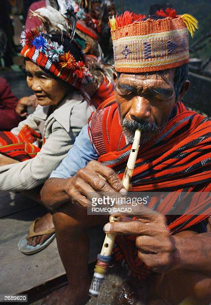 This photo dated 02 October 2003 shows Ifugao mountain tribesman Tomas Guinyang playing a bamboo flute beside elder tribeswoman Bugan Agudong in...