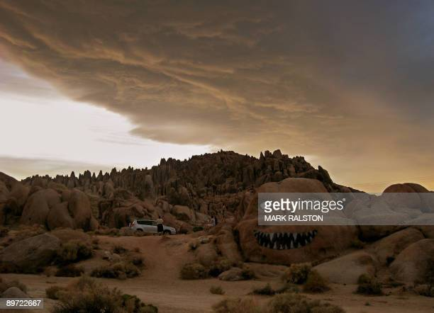 """This photo dated August 4, 2009 shows tourists at the """"Smiling Man"""" rock in the Alabama Hills near the town of Lone Pine in central California. The..."""
