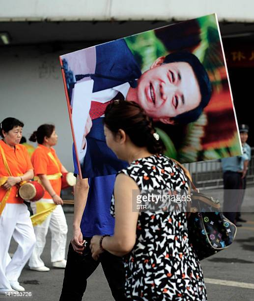 This photo dated June 29 2011 shows a Chinese woman carries a protrait of Bo Xilai until now a rising political star known for busting gangs and...