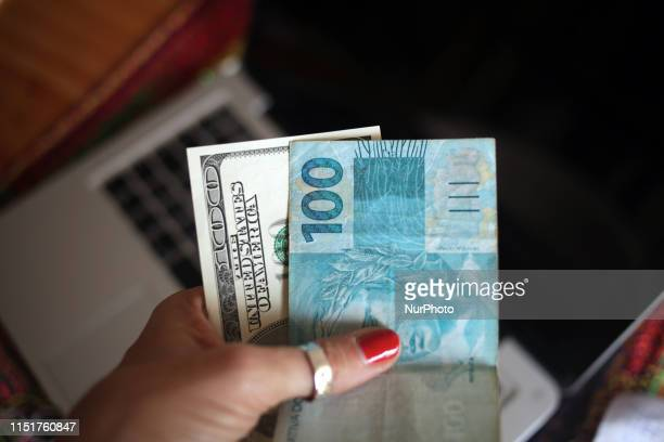This photo illustration show the USD Dollar and the Real Brazilian currency