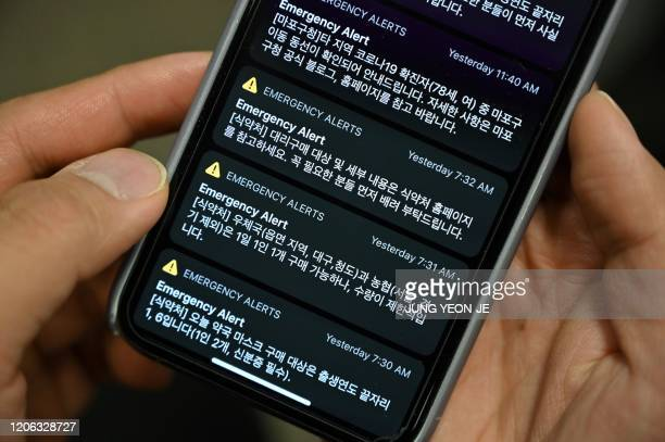This photo illustration shows a man holding her phone showing emergency alert text messages announcing locations that confirmed COVID19 patients have...