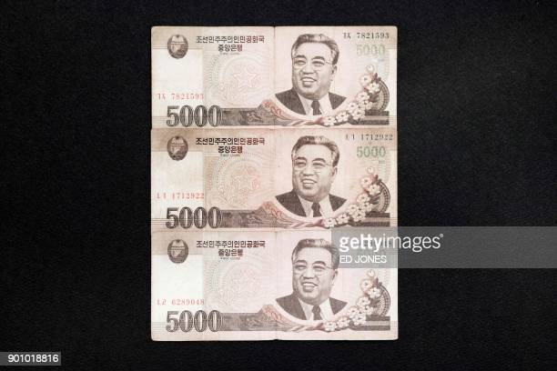 This photo illustration shows a selection of North Korean 5000 won currency bank notes featuring the image of late North Korean leader Kim IlSung...