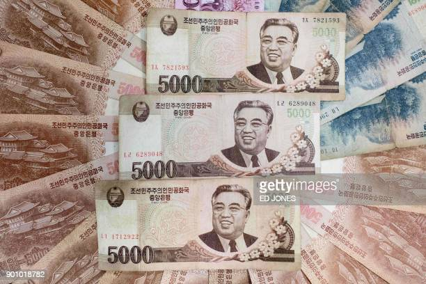 This photo illustration shows a selection of North Korean currency bank notes issued by Pyongyang displayed in Seoul on January 4 2018 At official...