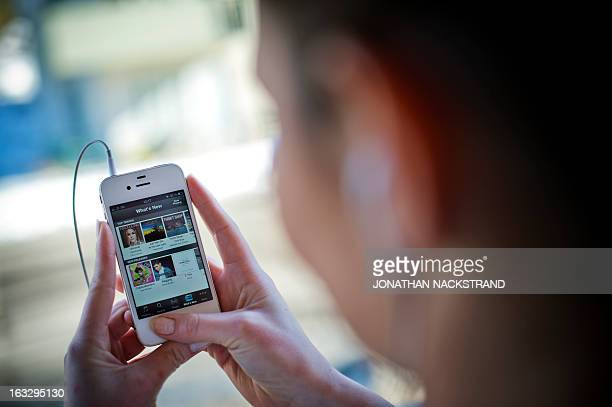 This photo illustration shows a woman as she uses the iPhone application of Swedish music streaming service Spotify on March 7 2013 in Stockholm...