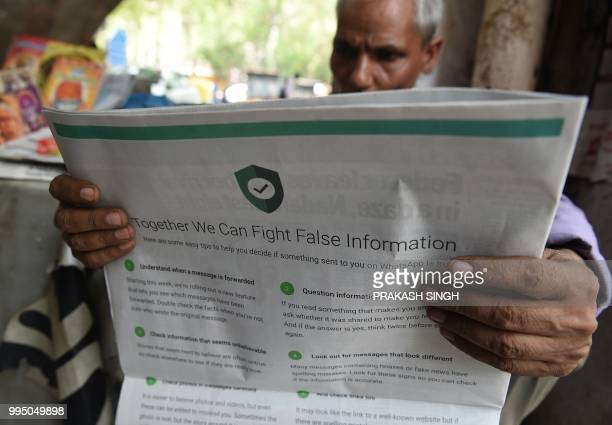 This photo illustration shows an Indian newspaper vendor reading a newspaper with a full back page advertisement from WhatsApp intended to counter...