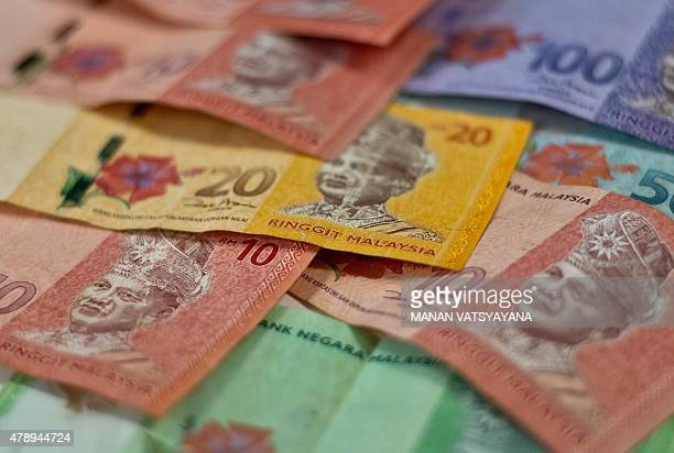 This photo illustration shows Malaysian ringgit banknotes in Kuala Lumpur on June 29 2015 Asian equities and the euro tumbled June 29 on fears Greece...