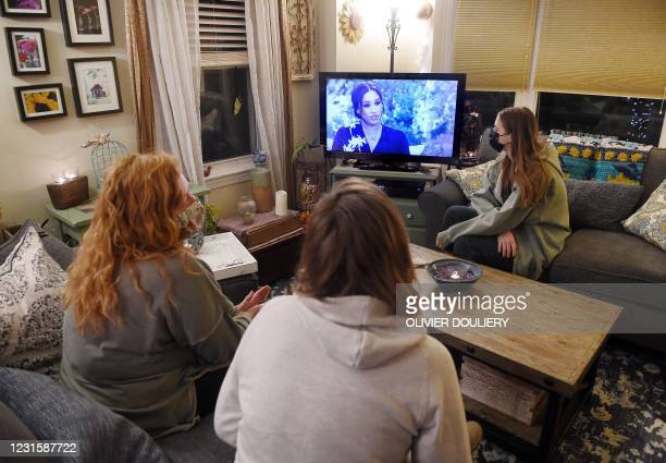 This photo illustration shows people wearing face masks, watch a televised conversation between Meghan Markle and US host Oprah Winfrey, in...
