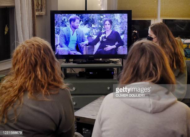 This photo illustration shows people wearing face masks, watch a televised conversation between Britain's Prince Harry with his wife Meghan Markle...