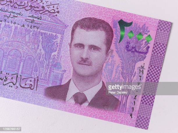 This photo illustration shows the face of President Bashar Assad on Syria's latest banknote next to an image of the Grand Umayyad Mosque photographed...