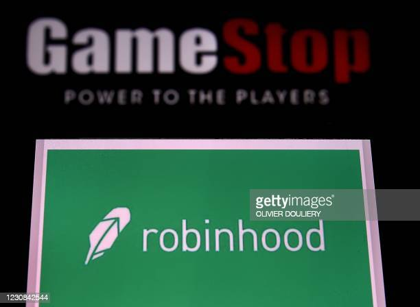 This photo illustration shows the logos of video grame retail store GameStop and trading application Robinhood on a computer and on a mobile phone in...