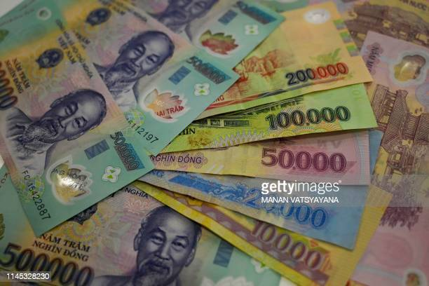 This photo illustration shows Vietnamese dong banknotes in Hanoi on May 21,2019.