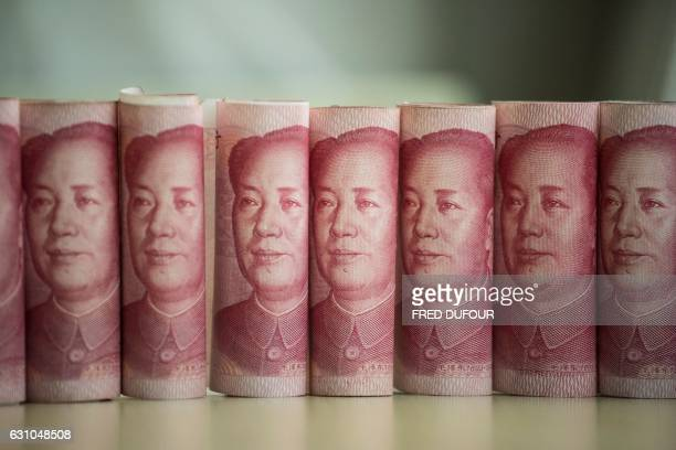 This photo illustration taken on January 6 2017 shows Chinese 100 yuan notes in Beijing China just raised the exchange rate for the yuan against the...