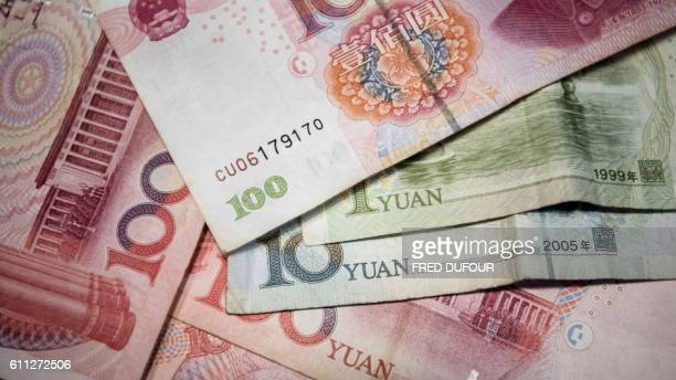 This photo illustration taken on September 29 2016 shows Chinese 100 yuan 10 yuan and one yuan notes in Beijing / AFP / FRED DUFOUR