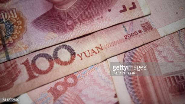 This photo illustration taken on September 29 2016 shows Chinese 100 yuan notes in Beijing / AFP / FRED DUFOUR