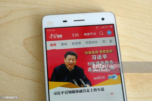 This photo illustratration taken on February 20 2019 shows a phone app called Xuexi Qiangguo or Study to make China strong with an image of China's...