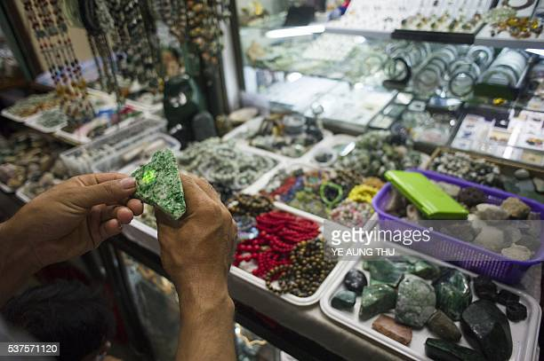 This photo is taken on June 1 2016 shows a man checking a Myanmar jade stone at a market at Yangon An embezzlement probe has been launched after...