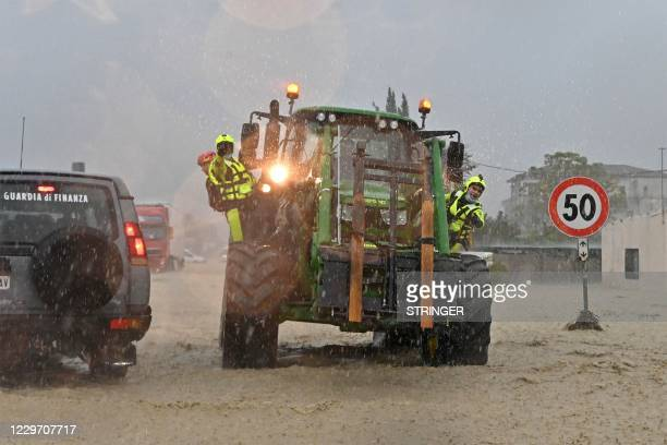 This photo obtained from Italian news agency ANSA shows rescuers using a tractor to move on across flooded roads in Crotone on November 21, 2020...