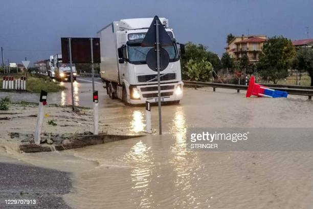This photo obtained from Italian news agency ANSA shows trucks driving across a flooded road in Crotone on November 21, 2020 following heavy rain. /...