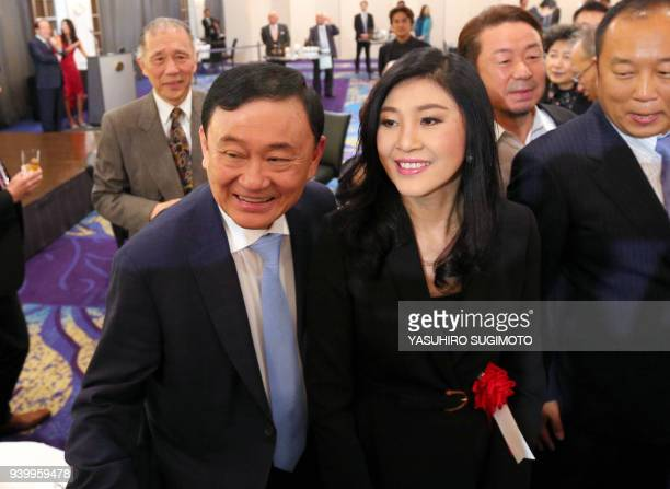 This photo received from Japan's Asahi Shimbun taken on March 29 2018 shows former Thai prime ministers Thaksin Shinawatra and his sister Yingluck...