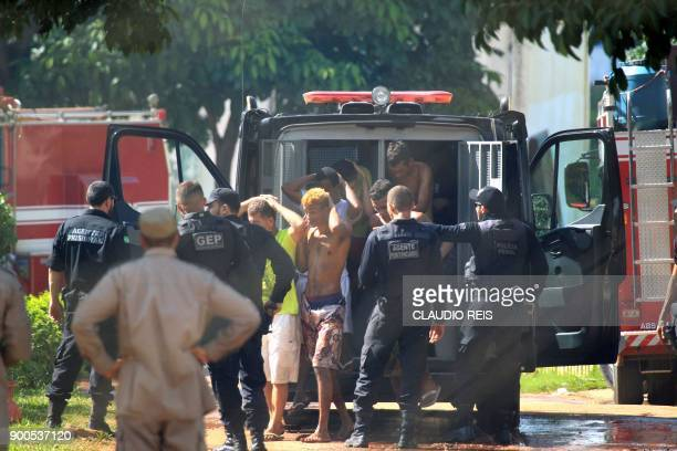 This photo released by Brazilian newspaper O Popular shows guards bringing prisoners back to the Coronel Odenir Guimaraes State Prison in Aparecida...