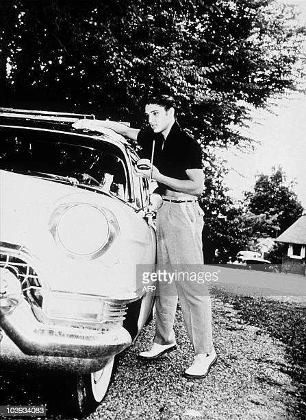 This photo released by Guernsey's Auction house shows US rock star Elvis Presley with his 1956 Lincoln Continental in this undated handout photo...