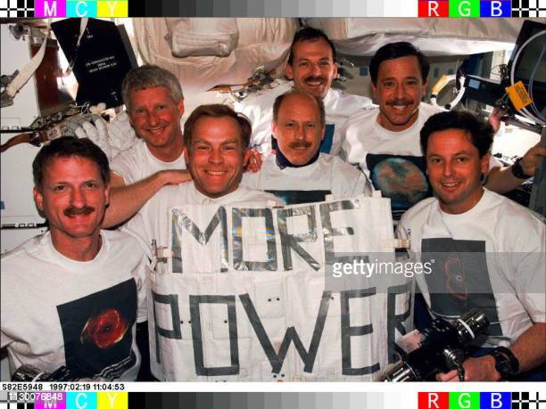 This photo released by NASA 19 February shows the crew of the Space Shuttle Discovery posing for a traditional inflight portrait after completing...