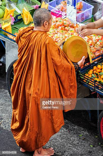 CONTENT] This photo represents a monk receiving his morning alms in the the streets of Bangkok Thailand