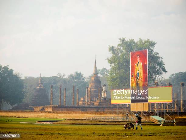 CONTENT] This photo shows a gardener working in park near to the king portrait and Wat Mahathat temple The Sukhothai Historical Park covers the ruins...