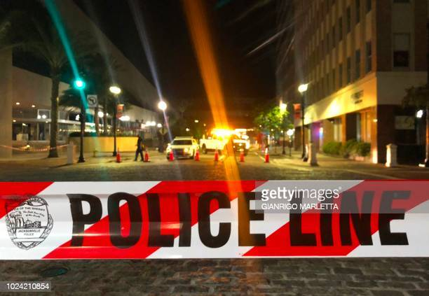 This photo shows a police car behind police tape blocking a street leading to the Jacksonville Landing area in downtown Jacksonville Florida August...