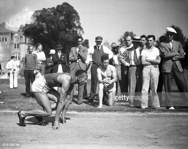 "This photo shows Jesse Owens, Ohio State's sensational athlete, in the ""et set"" position, as if he's about to sprint in a 100-yard dash."