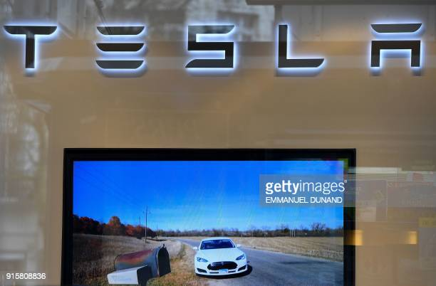 This photo shows the logo if US car maker Tesla above a screen at a store in Brussels on February 8 2018 A day after launching one of its cars into...
