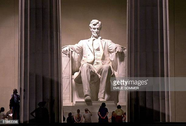 This photo shows visitors at the Lincoln Memorial in Washington DC 11 July 2001 The Lincoln Memorial on which construction began in 1915 was built to...