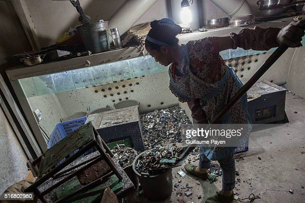 TOWN GUIYU GUANGDONG CHINA This photo shows workers heating up electronic component to remove computer chips in a recycling factory inside the well...