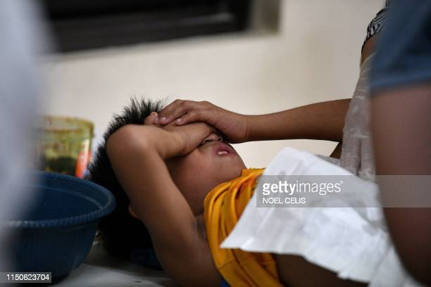 This photo take on May 10 shows a boy covering his eyes while being circumcised during a mass circumcision at a village health centre in Manila. - A...