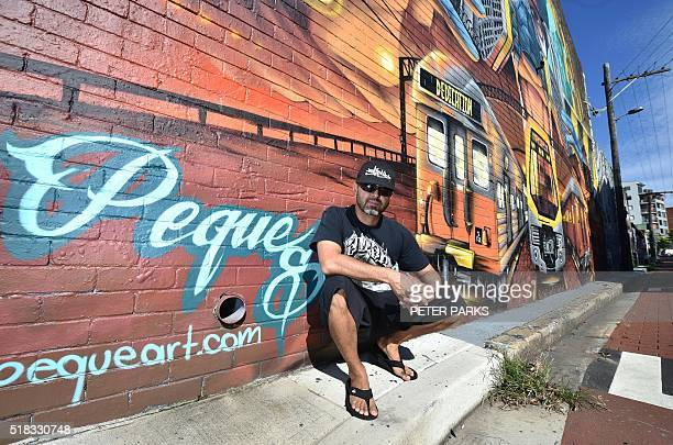 This photo takem on March 24 2016 shows MexicanAustralian artist Alejandro Martinez known as Peque standing in front of some of his street art in the...